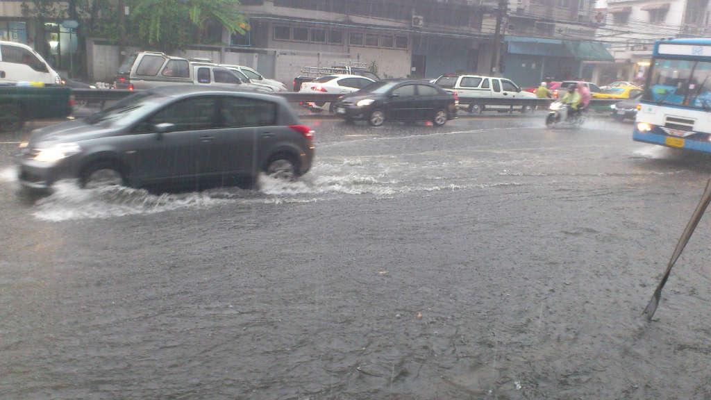 バンコクで洪水の中を走る車とバス