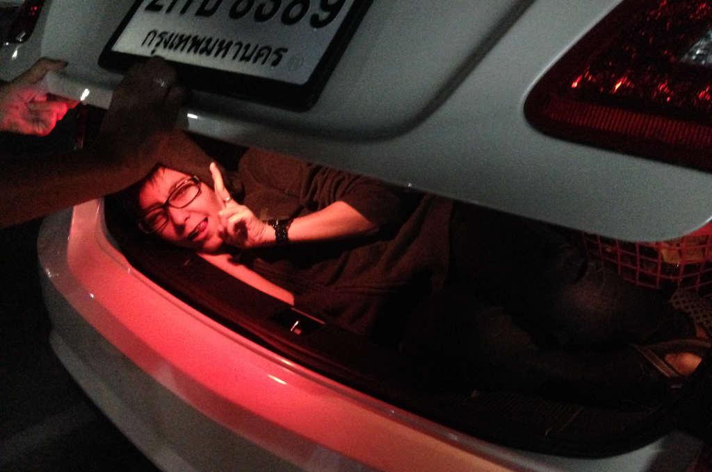 車のトランクの中で遊ぶタイ人